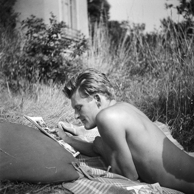 Le bel homme allongé et lisant