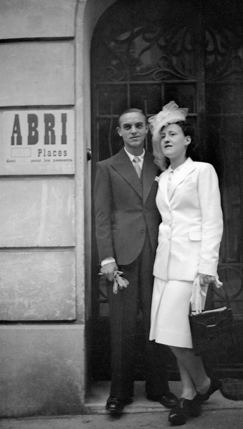 Mariés devant une porte d'immeuble.