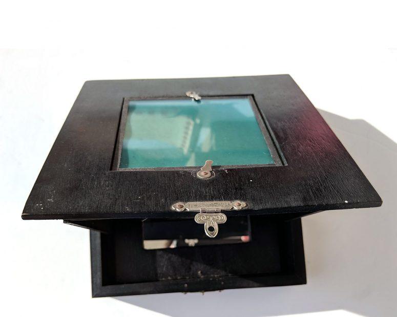 Ouverture de la visionneuse. Un carreau de verre teinté permet de corriger les couleurs en cas d'éclairage électrique
