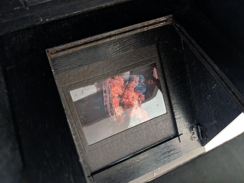 La visionneuse est placé face à une source de lumière qui va éclairer le film. Celui-ci se réfléchit sur le miroir, dans le bas de la visionneuse, bien contrasté sur le fond noir de l'appareil.